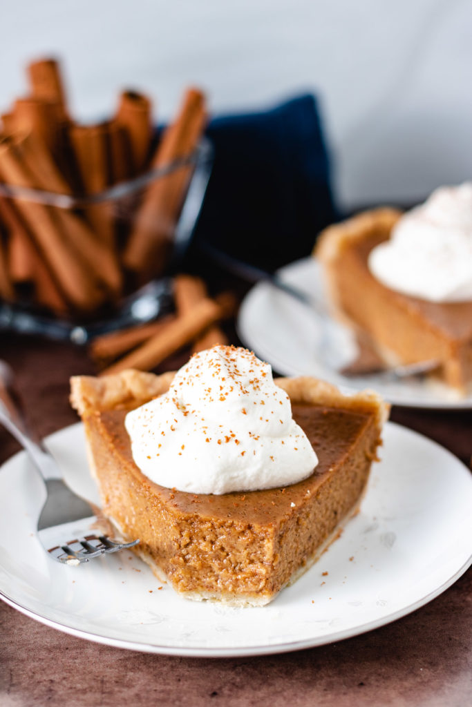 Pumpkin pie on a plate with a bite taken out.