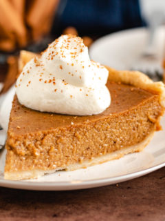 Pie with whipped cream and sprinkled cinnamon.
