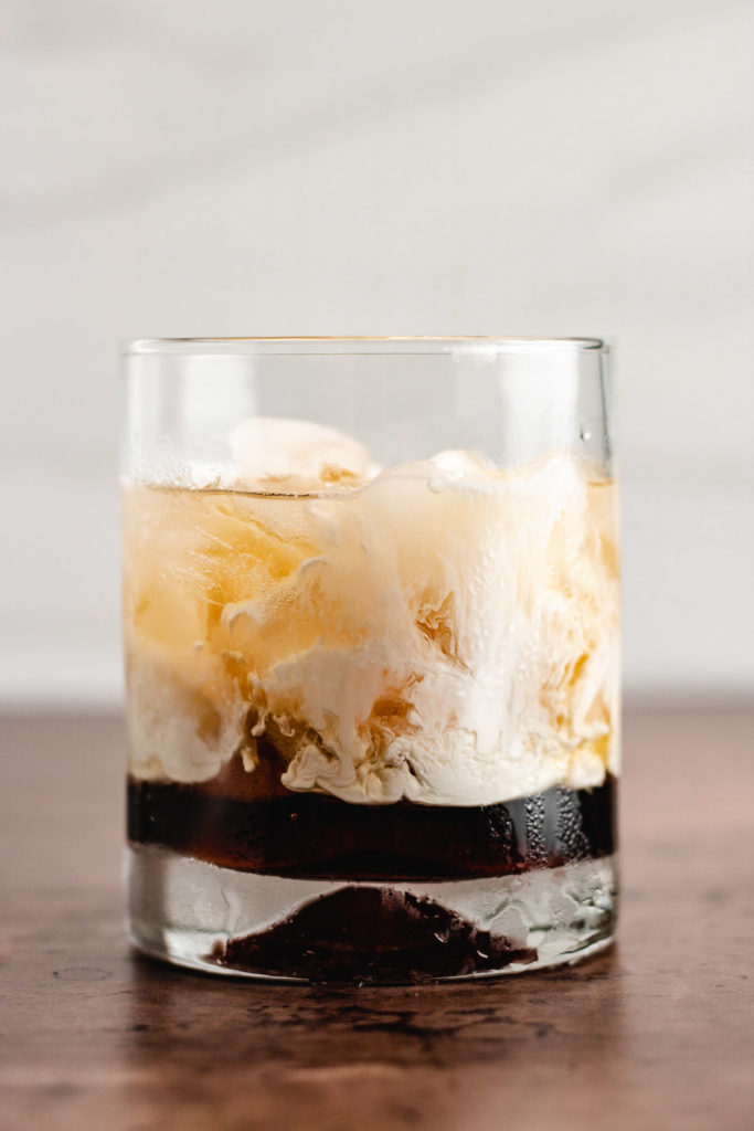 Cocktail glass filled with ice, liqueur, and heavy cream.