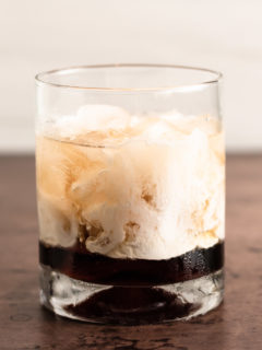 White Russian poured in a cocktail glass over ice.