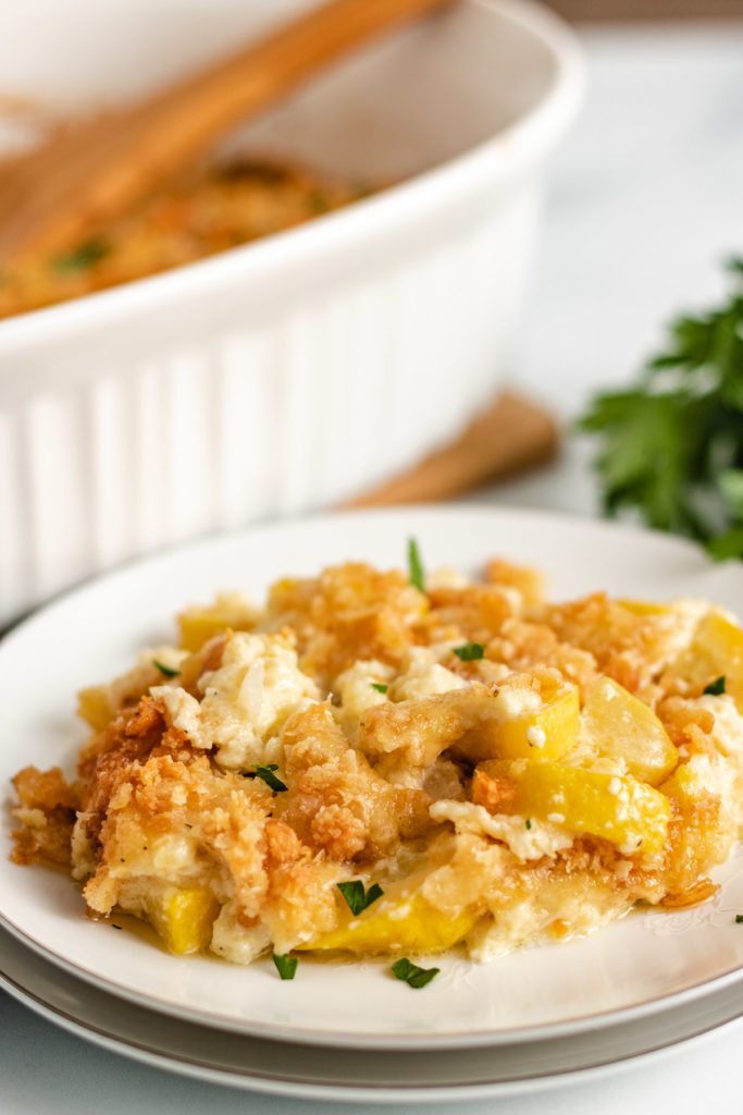 Yellow squash casserole on a white serving plate.