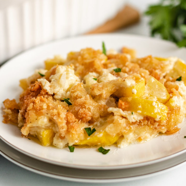 Yellow squash casserole served on a white plate.
