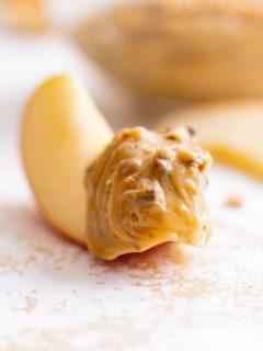 Apple slice dipped in caramel dip.