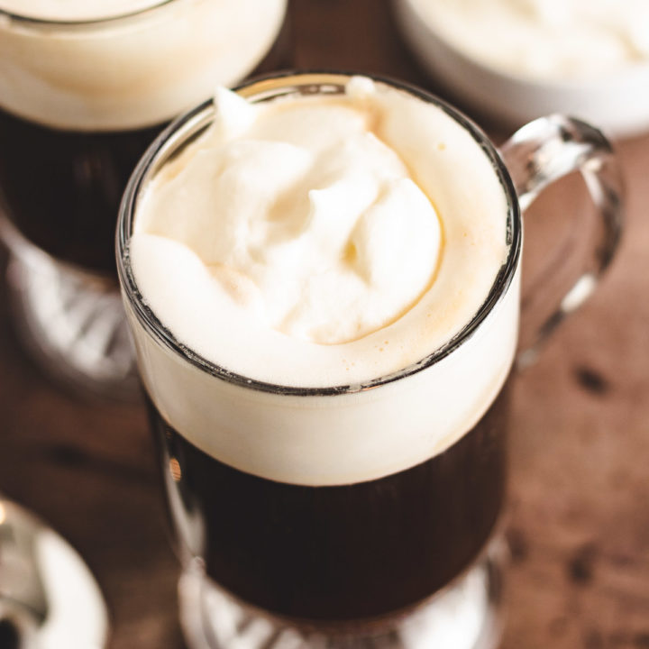 Top down view of dark coffee topped with whipped cream.