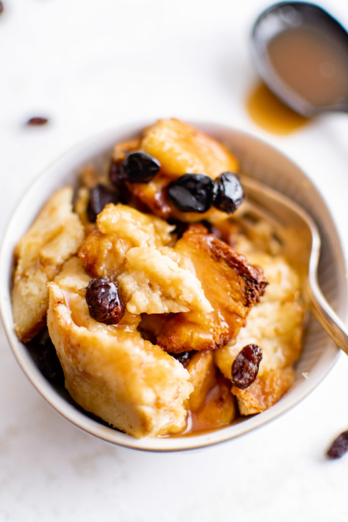 Caramel bread pudding with raisins in a bowl.