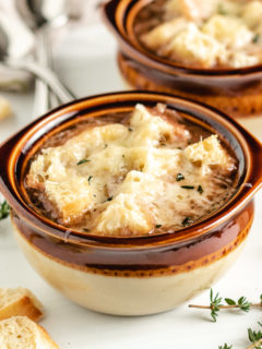 French onion soup in brown bowls.