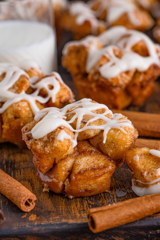 Monkey bread muffin next to a cinnamon stick.
