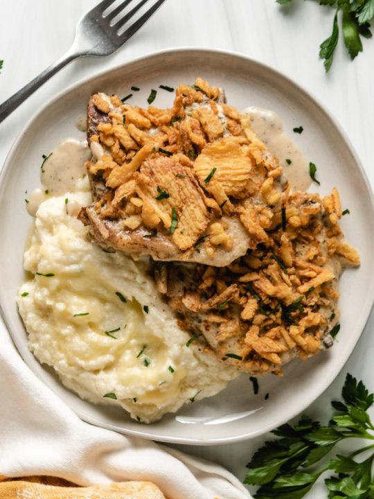 Top down view of two baked pork chops on a plate.