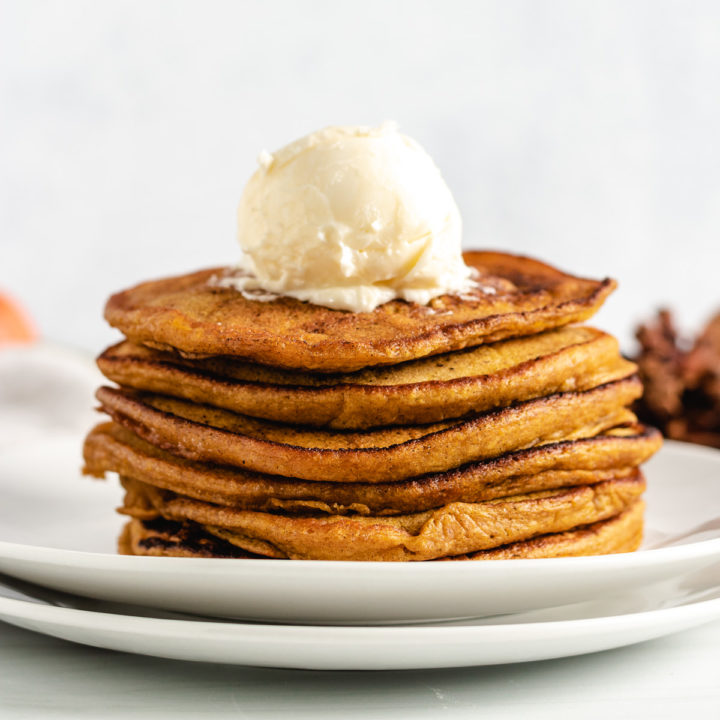 Pumpkin pancake stack with a scoop of butter.