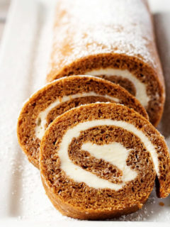 Pumpkin roll cake with powdered sugar on a white plate.