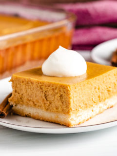 Square piece of pumpkin cheesecake on a plate.