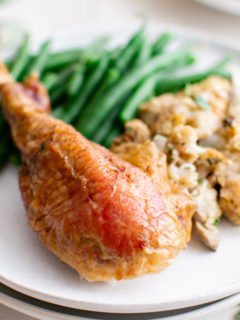 Roast turkey leg with green beans on a plate.